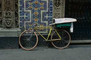 yellow bicycle and a talavera wall