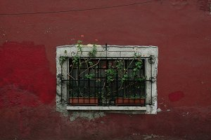 window in an old red wall