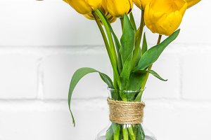 transparent vase with yellow tulips