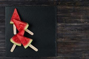 Watermelon slices on sticks.