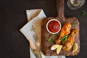 Grilled spicy chicken drumstick is served on a wooden board.