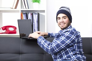 Young man hipster in the office with laptop in the office