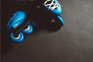Close up view of blue roller skates inline skate or rollerblading on dark tinted grunge backgroung