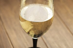 Glass of white wine on wooden table.