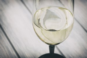 Close-up of white wine on wooden table.