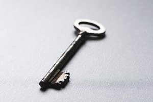 Old key on gray background.