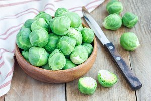 Fresh brussels sprouts in bowl on wooden background, horizontal
