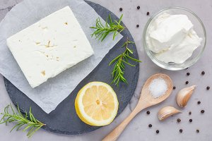 Ingredients for feta, cream cheese, rosemary, lemon and garlic dip on slate board, top view