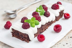 Homemade brownies with cream cheese frosting and raspberry, horizontal