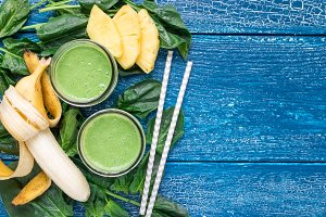 Detox green smoothie with spinach, pineapple, banana and yogurt, horizontal, flat lay, copy space