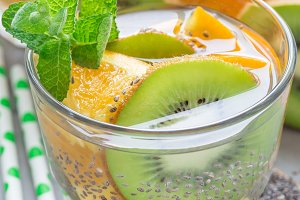 Healthy detox chia seed drink with kiwi, orange and mint in glass, vertical, closeup