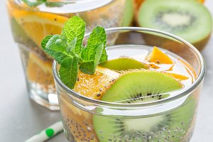 Healthy detox chia seed drink with kiwi, orange and mint in glass, vertical