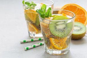 Healthy detox chia seed drink with kiwi, orange and mint in glass, horizontal, copy space