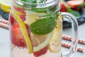 Healthy detox chia seed drink with strawberry, lemon and mint in jar, vertical