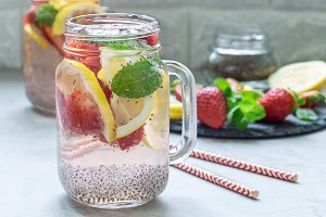 Healthy detox chia seed drink with strawberry, lemon and mint in glass jar, horizontal