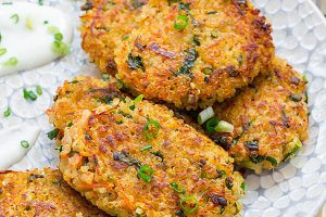 Vegetarian quinoa, carrot, coriander and green onion fritters served with yogurt, vertical