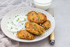 Vegetarian quinoa, carrot, coriander and green onion fritters served with yogurt on plate, copy space