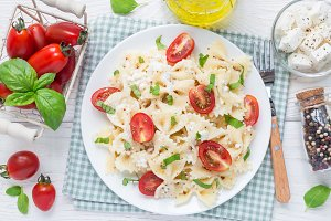Pasta salad with tie pasta, feta cheese, cherry tomatoes, mustard and basil, top view