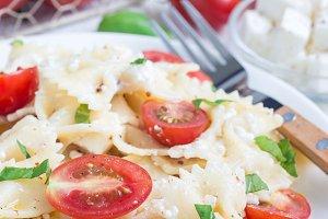 Pasta salad with tie pasta, feta cheese, tomatoes, mustard and basil, vertical