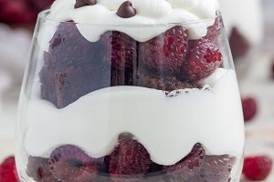 Trifle dessert with brownie, cream cheese frosting and raspberry in glass, vertical
