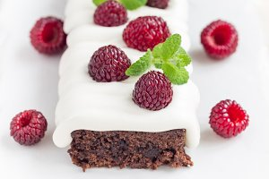 Homemade brownies with cream cheese frosting and raspberry
