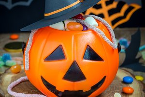 Halloween Jack o Lantern bucket overflowing with candy, spooky decorations on background, vertical