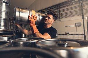 Brewer carrying metal beer barrel
