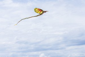 Kite flying in the sky among the clouds on the tropical Bali island, Indonesia.