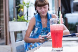 Fresh watermelon juice with mint, lemonade. Healthy drink for summer with vitamins, suits for vegetarian. Young women with smartphone on a blurred background.