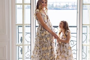 mother and daughter in matching dresses standing