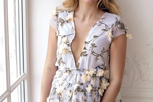 blonde girl in a long floral dress standing