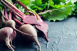 Young beets on dark stone table