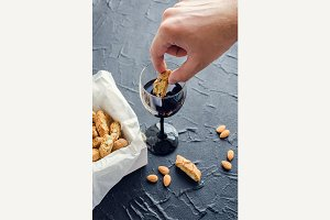 Hand dipping Italian cantuccini cookies into red wine
