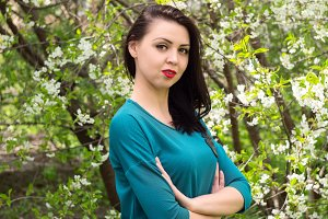 Young beautiful woman in spring blossoming garden