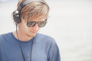Portrait of young man in headphones and sunglasses at the beach