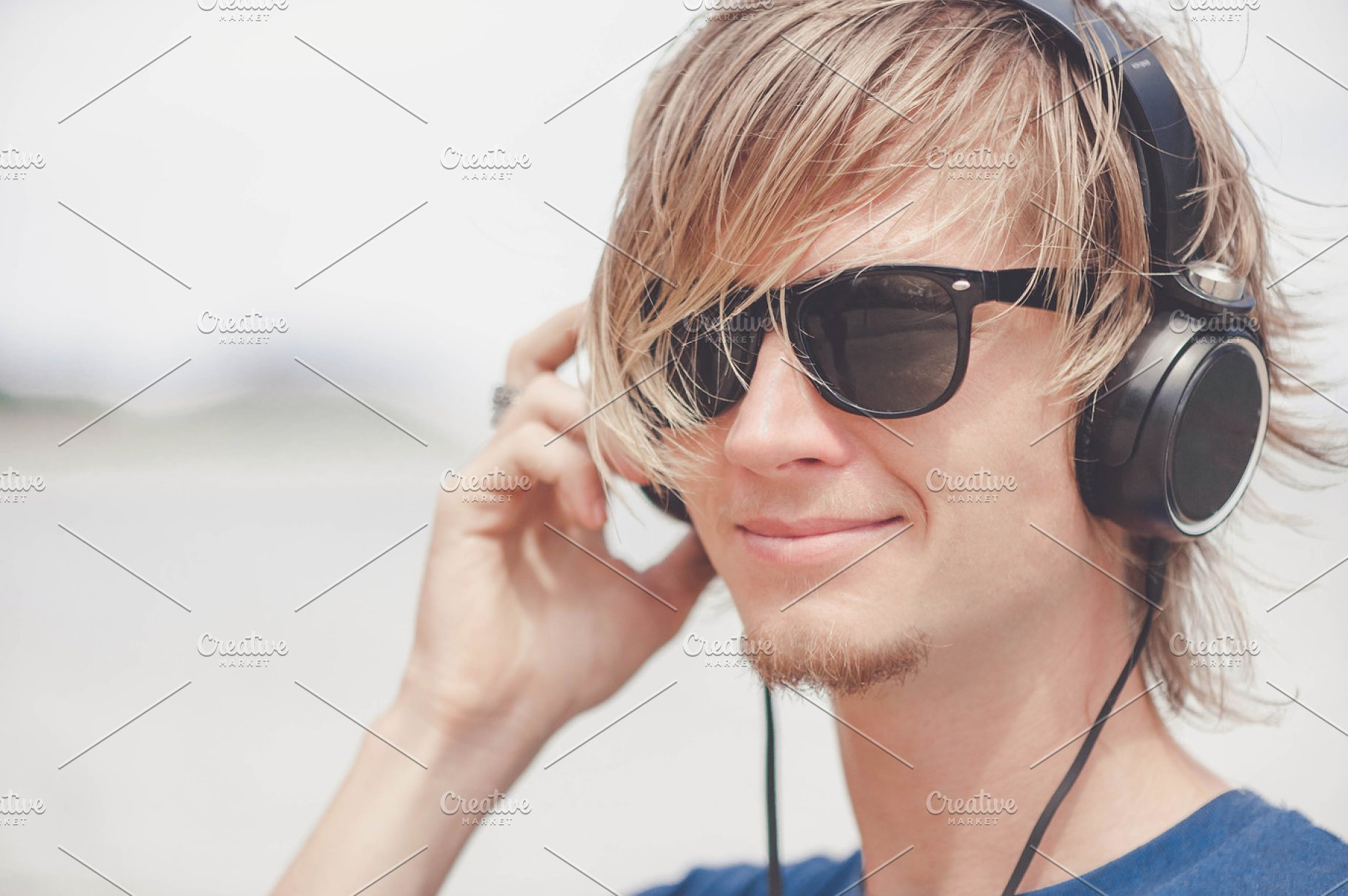 d34b6ccdfab6 Portrait of young man in headphones and sunglasses at the beach ...