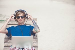 Handsome blonde man working with laptop and headphones at the beach