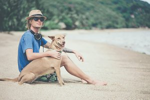 Young handsome man wearing blue t-shirt, hat and sunglasses, sitting on the beach with the dog