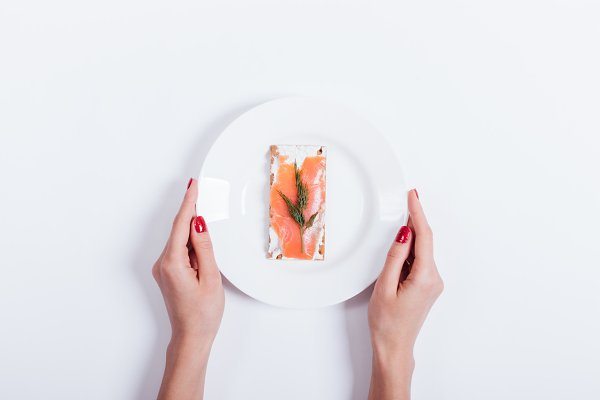 Female hands holding a plate of foo…