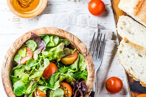 Vegetarian salad with lettuce and tomatoes in olive wooden bowl