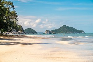 Outdoor landscape of beautiful secret tropical sea beach with gorgeous water in Khao Sam Roi Yot National Park, Thailand. Perfect vacation in Southeast Asia at exotic white sand beach and palm trees.