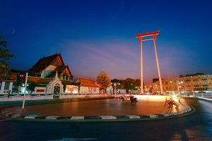 The Giant Swing with Temple of Buddha at dusk. Bangkok night city downtown, Thailand. Modern night city skyline with lights reflection, Asia