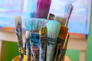 Group of used brushes in bucket