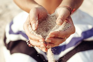 Female hands holding sand