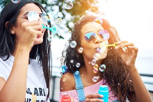 Playful young girlfriends blowing bubbles outside in summer