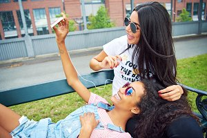 Laughing young girlfriends taking selfies on bench outside
