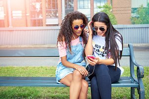 Two smiling girlfriends sitting outside listening to music on earphones