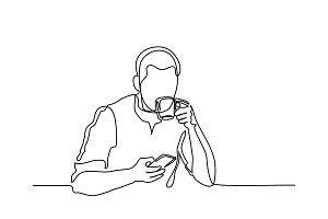 Young man browsing cell phone and drinking coffee