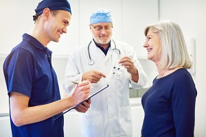 Doctor talking to woman while smiling assistant writing in tablet