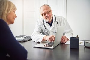 Diagnosis specialist talking to woman showing her laptop